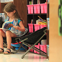 Alinea Loague, a kindergartner in Candice Bishop's class at Saltillo Primary School, sits and looks through a book as she waits on the first day of school to get started on Thursday morning.
