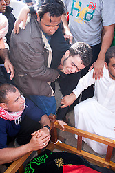 © under license to London News Pictures.  18/02/2011. The brother of Ali Al Almoumen, the third person to be buried in Sitra today, weeps over his grave has he was buried. Al Almourmen was killed on Wednesday at the Pearl Roundabout.  Photo credit should read Michael Graae/London News Pictures