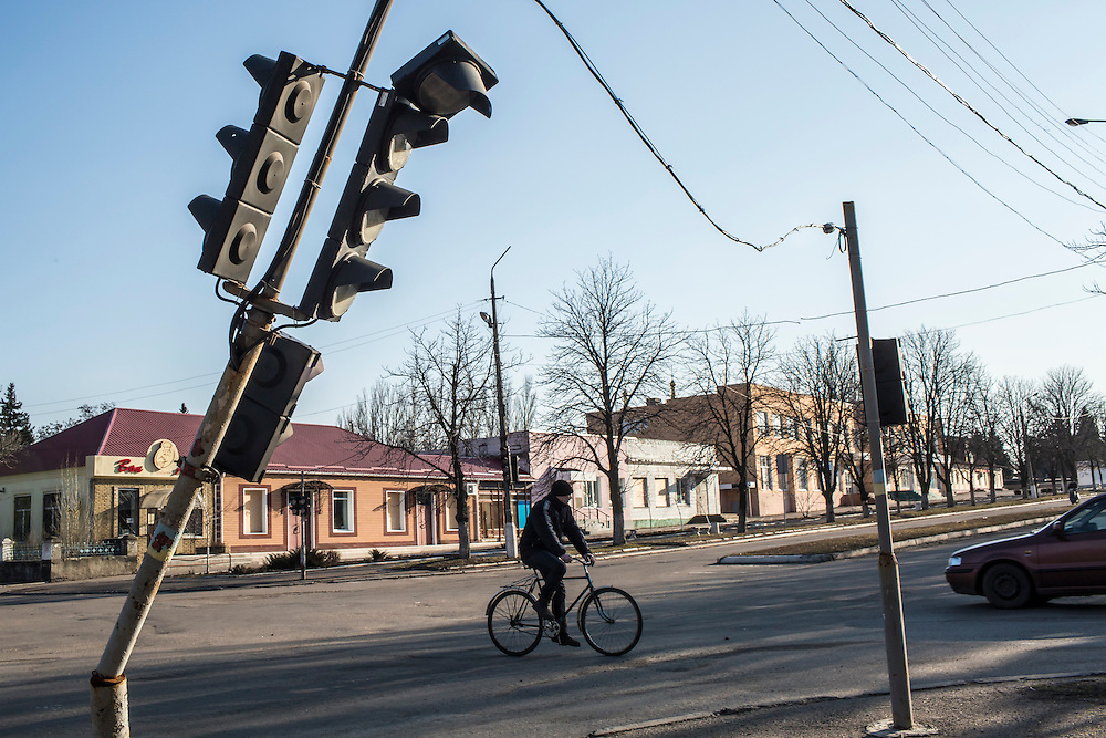 MARIINKA, UKRAINE - FEBRUARY 20, 2016:  A man rides a bicycle in Mariinka, Ukraine. The Donetsk suburb has been the scene of some of the heaviest fighting recently between Ukrainian forces and pro-Russian rebels. CREDIT: Brendan Hoffman for The New York Times