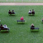 Spectators sit on benches at Royal Ascot, during the Royal Ascot race meeting. Royal Ascot. England, UK. June 16-20th, 2009. Photo Tim Clayton