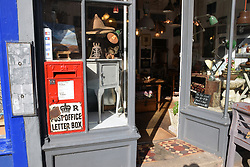 Working Victorian letter box in the window of an antiques shop (formerly post office) in Upper St Giles Street, Norwich, UK