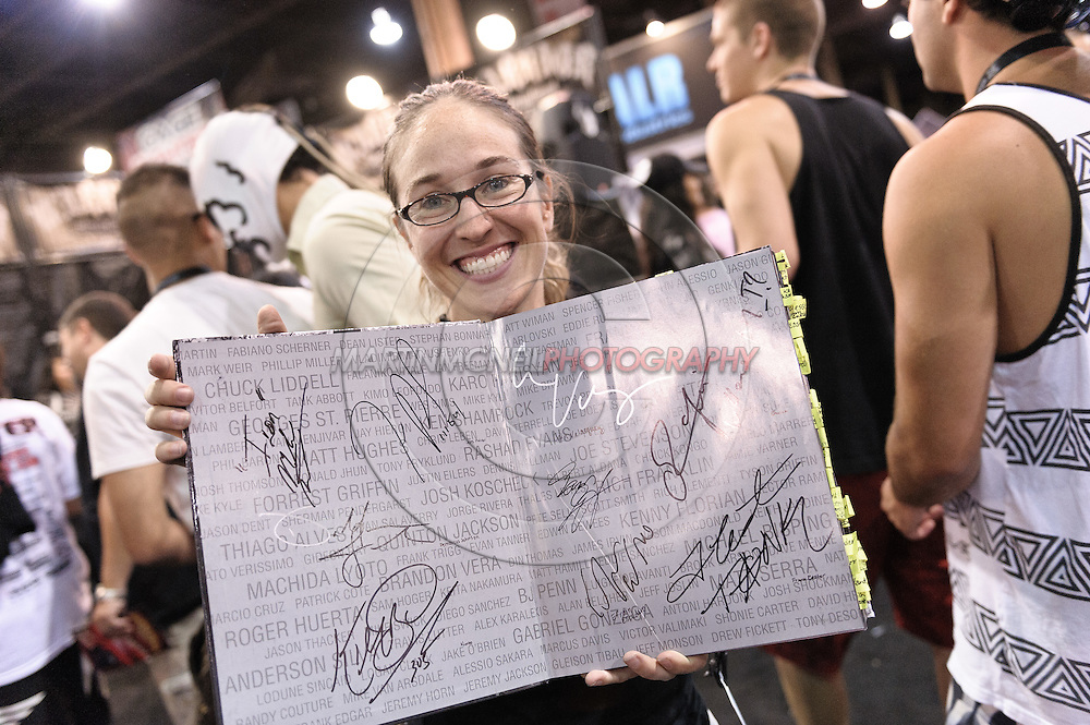 "LAS VEGAS, NEVADA, JULY 10, 2009: A fan proudly displays fighter autographs that she has collected in her copy of Kevin Lynch's book ""Octagon"" during the UFC Fan Expo inside the Mandalay Bay Convention Centre in Las Vegas, Nevada"