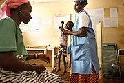 A nurse carries Kambou Sansan, 4, a malnourished boy, during a visit at the Panzarani health center in the village of Panzarani, Zanzan region, Cote d'Ivoire on Friday November 25, 2011.