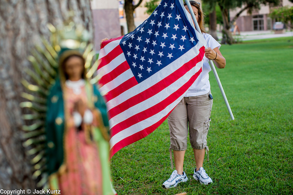 """19 JULY 2012 - PHOENIX, AZ:  MARIA URIBE unfurls an American flag at the Arizona Capitol during a vigil the first day of a class action lawsuit, Melendres v. Arpaio in Phoenix Thursday. The suit, brought by the ACLU and MALDEF in federal court against Maricopa County Sheriff Joe Arpaio, alleges a wide spread pattern of racial profiling during Arpaio's """"crime suppression sweeps"""" that targeted undocumented immigrants. U.S. District Judge Murray Snow granted the case class action status opening it up to all Latinos stopped by Maricopa County Sheriff's Office deputies during the crime sweeps. The case is being heard in Judge Snow's court.  PHOTO BY JACK KURTZ"""