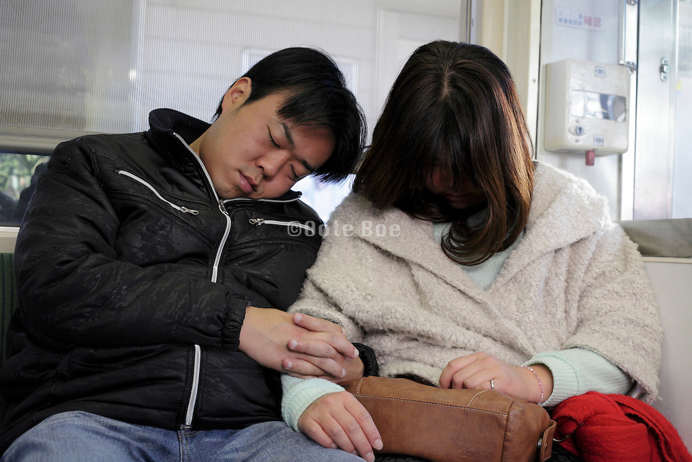 couple sleeping during train commute Japan