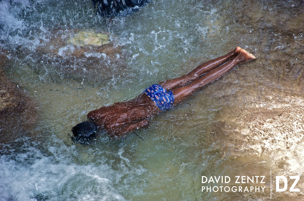 A boy submerges himself in the cleansing waters of Saut D'eau during the annual 3-day voodoo pilgrimage held there on July 14, 2008