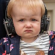 NLD/Amsterdam/20190803 - Gaypride 2019, kindeje langs de kade met haar moeder, met een koptelefoon als bescherming tegen de harde muziek