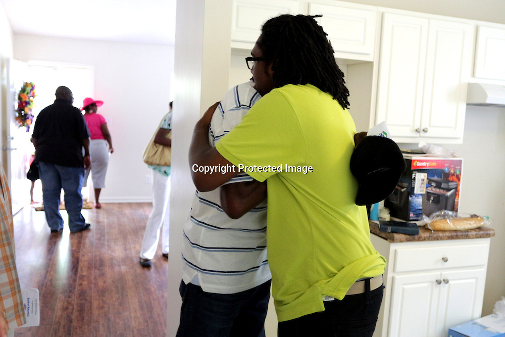 Homeowner Christian Pierce, right, receives a hugs from family friend Doug Carlos Sunday June 22, 2014 during a Cape Fear Habitat for Humanity dedication ceremony of a recently completed home on Tiffany Drive in Wilmington, N.C. (Jason A. Frizzelle)
