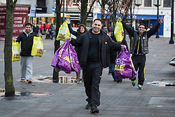 © Licensed to London News Pictures . 26/12/2013 . Manchester , UK . Shoppers with Next bags cross Piccadilly Gardens in Manchester City Centre . Thousands of shoppers queue for hours in freezing temperatures in Manchester this Boxing Day morning (26th December 2013) in order to be amongst the first to purchase reduced price products in shops' sales . Photo credit : Joel Goodman/LNP