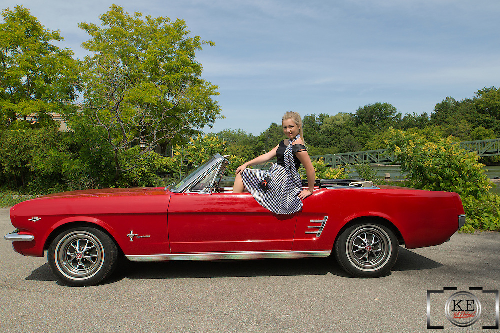 A pretty young blonde in a poodle skirt on a 1966 Ford Mustang convertible 289.