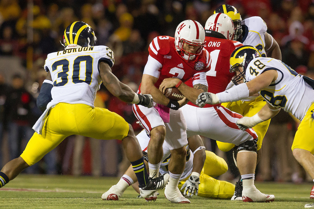 Thomas Gordon (30) and Desmond Morgan (48) of the Michigan Wolverines tackle quarterback Taylor Martinez (3) of the Nebraska Cornhuskers during Nebraska's 23-9 victory over Michigan on Oct. 27, 2012 at Memorial Stadium in Lincoln, Neb.