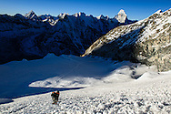 A party of climbers start the ascent of the main Ice Wall on Island Peak. Makalu (left) and Ama Dablam (Right) can be seen on the horizon.