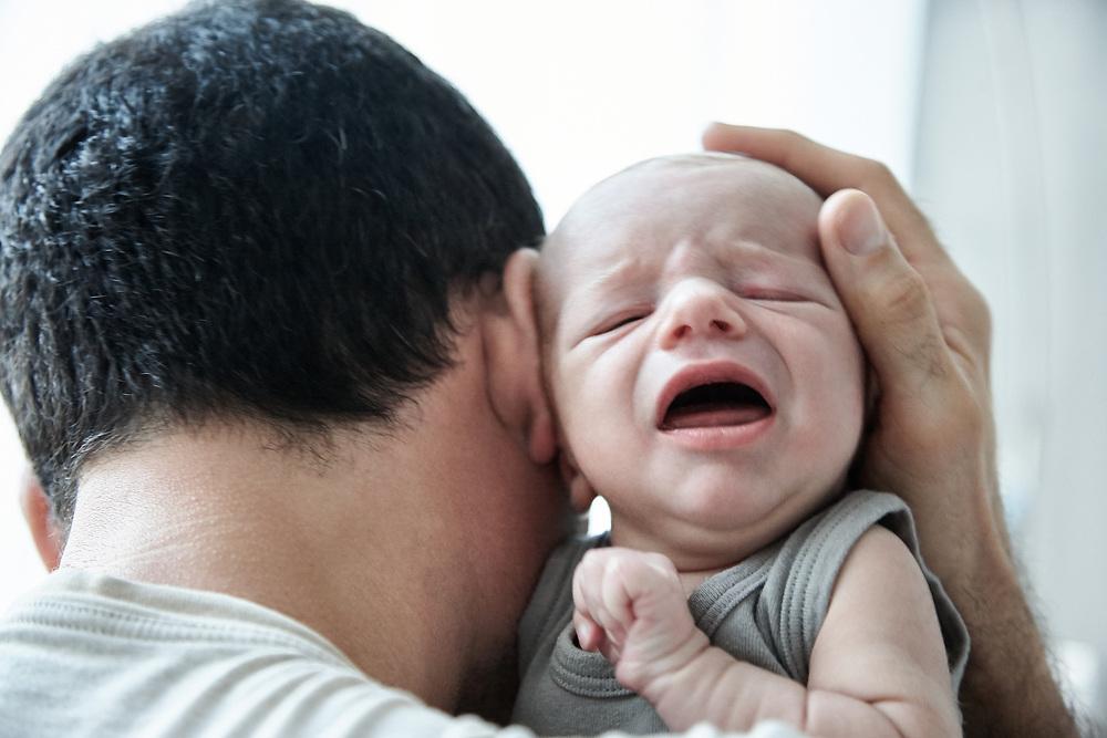 Dad comforting crying new born