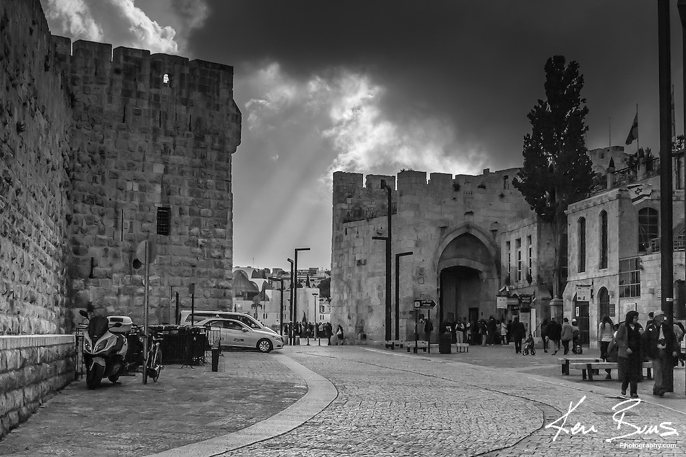 The sun streaming from behind the clouds at Jaffa Gate in The Old City of Jerusalem. Jaffa Gate is one of 8 entrances to the Old City and is the only gate at a right angle to the city wall.<br /> <br /> The Gate is located off of Omar Ben el-Hatab close to the Tower Of David.