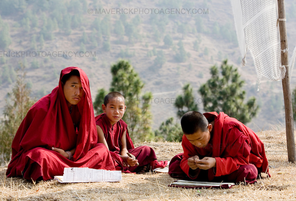 Young monks study outdoors at the Temple of Fertility built by Divine Madman. Punakha..Commonly described as the last Himalayan Shangrila, Bhutan is a country of unique serenity, harmony, and beauty. Nestled between India, China, and Tibet, this independent country whose name translates as 'the Land of the Thunder Dragon' has for the past 300 years  proactively followed a policy of isolation and cultural protection. Travel in and out of the country is strictly regulated, and the impact of outside influences on the local culture is carefully monitored. Spirituality is an important aspect of Bhutanese culture, with Buddhism being interlinked with everyday life. Gross National Happiness (GNH), as opposed to GNP/GDP, forms the cornerstone of its development strategy which focuses on a holistic development strategy that complements its cultural and Buddhist spiritual values.