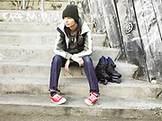 Young woman sitting on steps with rollerblades next to her.
