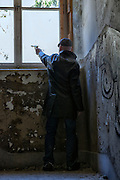 a man in dark clothes is shooting out of a window in an old, abandoned building