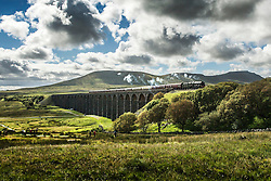 © Licensed to London News Pictures. 07/07/2016. Ingleton UK. File picture taken 26/08/2015 shows a train passing over Ribblehead Viaduct. After heavy rainfall in February caused a 500,000 ton land slip on the Settle to Carlisle railway which includes the world famous Ribblehead Viaduct the line has been partly closed, now a £23M repair project will see hundreds of concrete filled steel tubes set into the hillside to form a corridor on which a 100 metre long concrete slab will be placed to give the railway a solid base and the line will be fully re-opened next year. Photo credit: Andrew McCaren/LNP