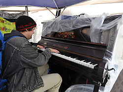 © Licensed to London News Pictures. 26/10/2011. London, UK. A protester plays a piano in a tent.  Occupy London protesters outside St Paul's Cathedral today, 26 October 2011. The UK's most popular Cathedral still has its doors closed over health and safety fears for it's visitors. Photo: Stephen Simpson/LNP