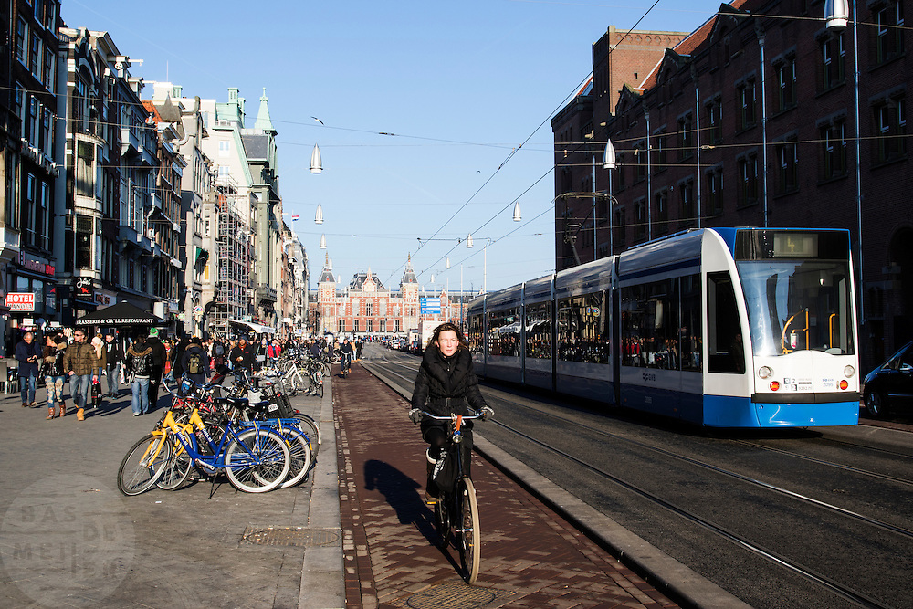 In Amsterdam fietst een vrouw over het fietspad op het Damrak, een tram rijdt over de trambaan. Het Damrak is onlangs opnieuw ingericht met een duidelijkere scheiding tussen fietsers, trams en auto&rsquo;s.<br /> <br /> In Amsterdam a woman rides on the bike lane on the Damrak, a tram is passing by. The Damrak is newly redesigned with a clearer separation between cyclists, trams and cars.