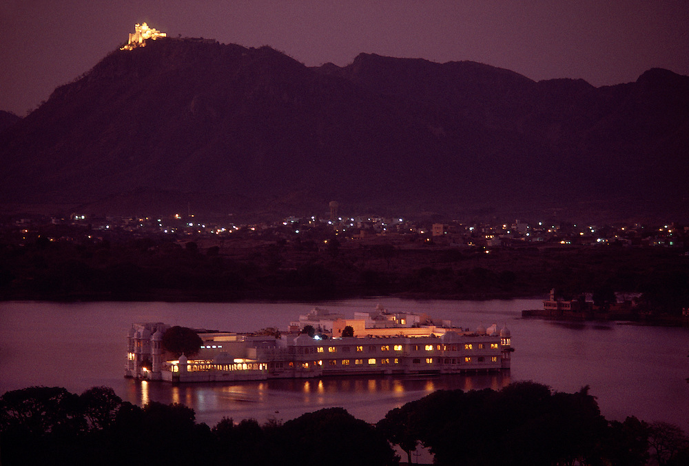 The Lake Palace Hotel on Lake Pichola at twilight (the Monsoon Palace on top of the mountain in the background), Udaipur, Rajasthan, India