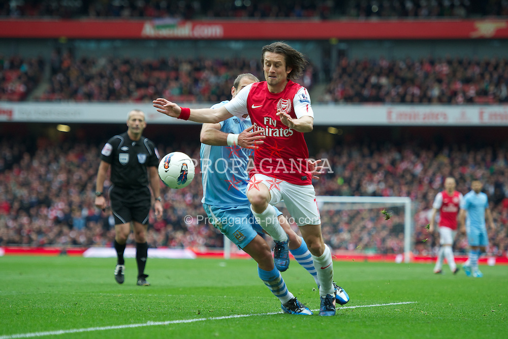 LONDON, ENGLAND - Easter Sunday, April 8, 2012: Arsenal's Tomas Rosicky is pulled by back Manchester City's Pablo Zabaleta during the Premiership match at the Emirates Stadium. (Pic by David Rawcliffe/Propaganda)