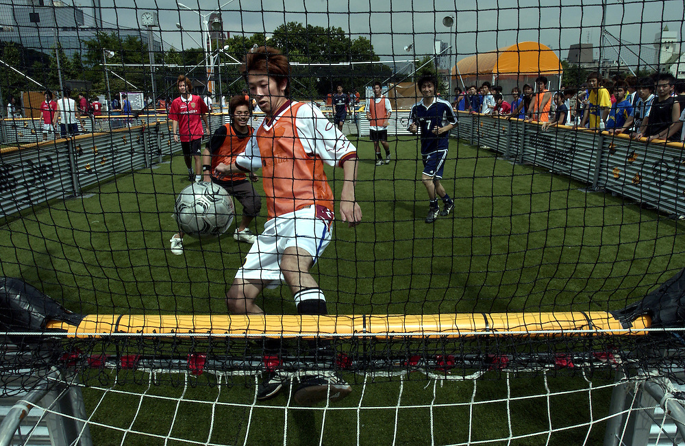 Japanese soccer players battle it out in a three on three knockout tournament at Nike Park in Harajuku, Tokyo. FIFA World Cup 2002 Tokyo Japan June 2002..©David Dare Parker/AsiaWorks Photography