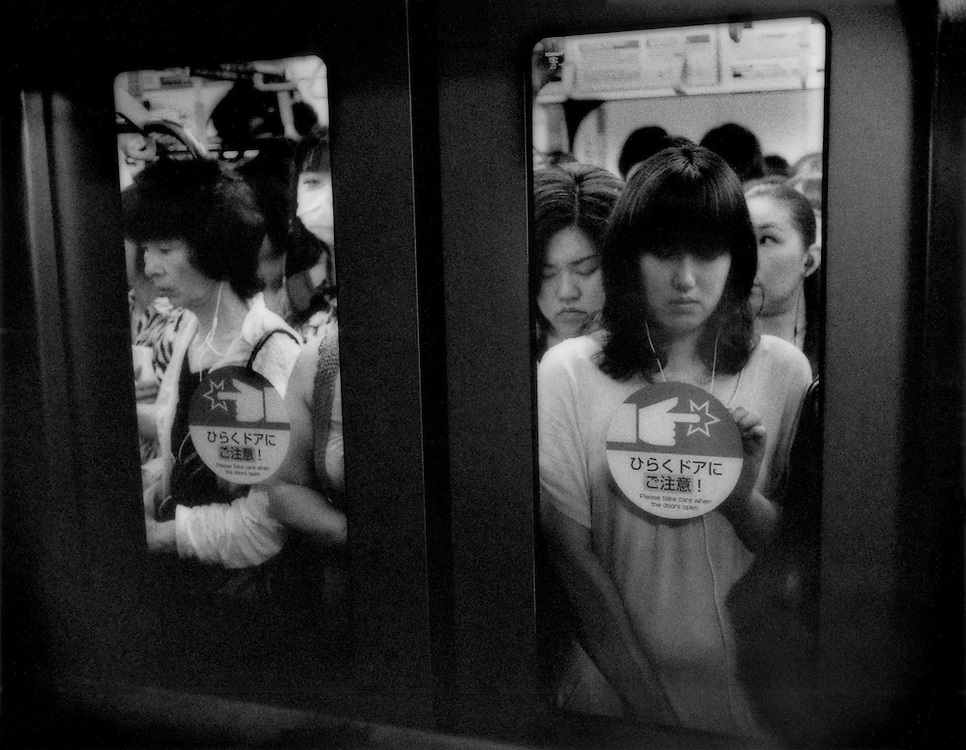 Privacy, Isolation / Japanese people are masters at finding a little peace in urban chaos and et plenty of practice ignoring their immeditate neighbors, whether in a train or in the apartment or house next door.  On crowded commuter trains, people tend to shut out the crush of humanity by diving into their own little private bubble, which can involve staring into their mobile phone, choosing an unoccupied spot on the wall to stare at, or simply staring at the train floor, Tokyo, Japan.
