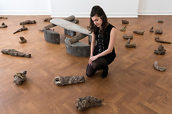 "© Licensed to London News Pictures. 17/04/2018. LONDON, UK. A staff member views 38 clay sculptures called ""Urtiere (Primordial Animals)"", 1958/1982, with ""Hirsch (Stag)"", 1958/1982, a teak wood and wooden ironing board that belonged to the artist's mother behind her, at the preview of ""Joseph Beuys: Utopia at the Stag Monuments"", at the Galerie Thaddaeus Ropac in Dover Street.  The retrospective is the most important UK exhibition of Beuys' work in over a decade, presenting major sculptures and rarely seen works from 1947 to 1985, and runs from 18 April to 16 June.  Photo credit: Stephen Chung/LNP"