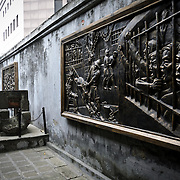 At right and in the distance, mounted on the wall, are bronze murals depicting the harsh conditions for prisoners at Hoa Lo Prison under French colonial rule. At left is an example of the very small drainage tunnel that several prisoners escaped through. Hoa Lo Prison, also known sarcastically as the Hanoi Hilton during the Vietnam War, was originally a French colonial prison for political prisoners and then a North Vietnamese prison for prisoners of war. It is especially famous for being the jail used for American pilots shot down during the Vietnam War.