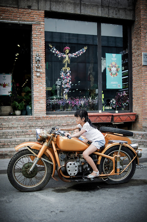 A chinese girl plays with a motorbike in the streets of 798 Art District in Beijing, China, July 19, 2014. <br /> <br /> 798 Art District (Chinese: 798艺术区; pinyin: 798 Yìshùqū), or Dashanzi Art District, is a 50-year old decommissioned military factory buildings with unique architectural style. Located in Chaoyang District of Beijing, that houses a thriving artistic community. Since the beginning of 2000, 798 has become a centre for art galleries, artists's ateliers and contemporary arts exhibitions. The buildings are within alleys number 2 and 4 on Jiǔxiānqiáo Lù (酒仙桥路), south of the Dàshānziqiáo flyover (大山子桥). <br /> <br /> © Giorgio Perottino