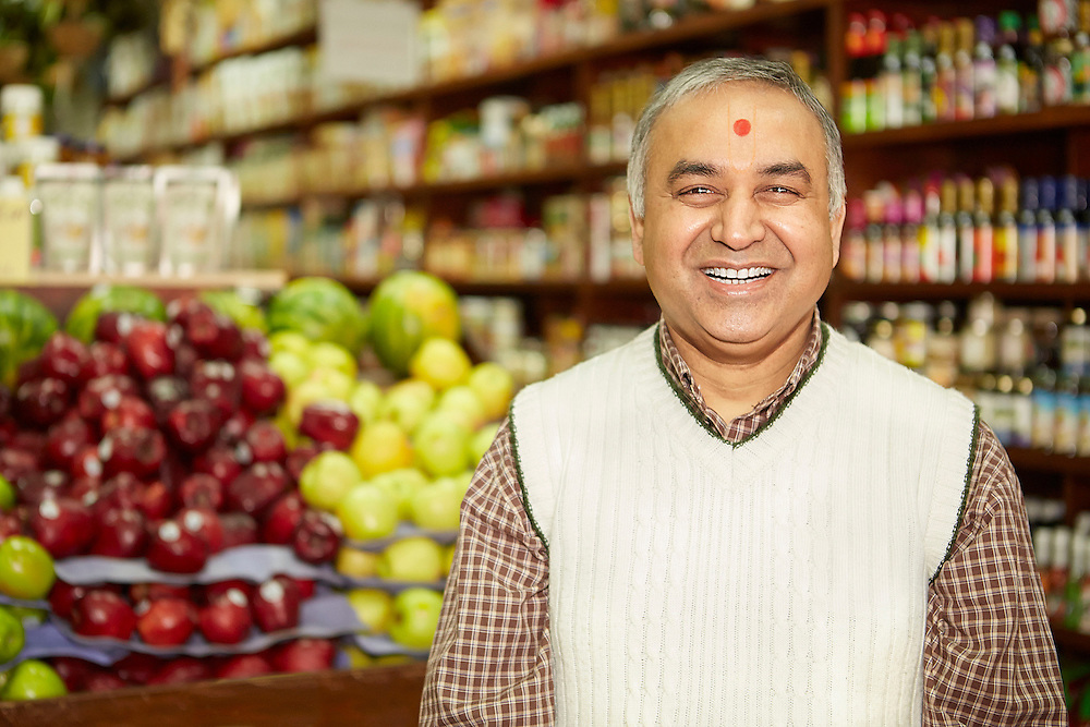 Portrait photograph of senior Indian shopkeeper with smile in his organic vegetable store