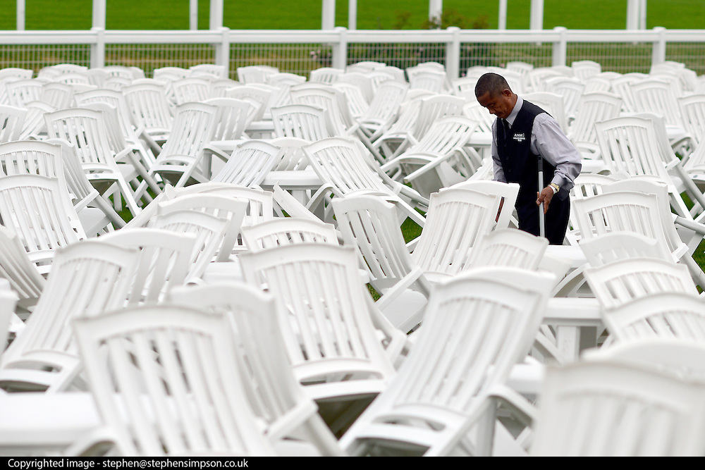 © London News Pictures. 20/06/2013. Ascot, UK. A man prepares a seating area. Ladies Day on day three of Royal Ascot at Ascot racecourse in Berkshire, on June 20, 2013. The 5 day showcase event, which is one of the highlights of the racing calendar, has been held at the famous Berkshire course since 1711 and tradition is a hallmark of the meeting. Top hats and tails remain compulsory in parts of the course.  Photo credit : Stephen Simpson/LNP