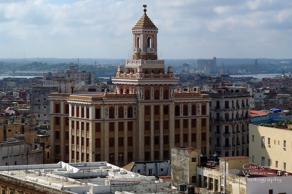 "Built in 1930, the Bacardi building's art deco maginificence still rises above historic Old Havana, an architectural treasure. The famous ""black bat on red globe"" that is the Bacardi logo adorns the building's cupola.  This view of the Bacardi building from an upper floor of the Hotel Sevilla looks east over the city, the bay, and East Havana beyond."