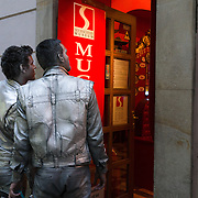 Painted silver from head to toe, a pair of street performers pause to look through the doorway of the Sex Machines Museum as they make their way to the old town square at the centre of Prague, capital of the Czech Republic, on 11 November 2014.
