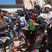 Rival villagers clash in the streets of Macha during the Tinku Festival. Macha, Bolivia, 4th May 2010, Photo Tim Clayton ..Each May, up to 3000 thousands indigenous Bolivian indians descend on the isolated mountainous village of Macha 75 miles north of Potosi in the Bolivian Andes. The 600 year old pre-hispanic Bolivia Festival of Tinku sees villagers from all over the region march into town to be pitted against each other in a toe to toe fist to fist combat.. They dance and sing in traditional costume and drink 96% proof alcohol along with chicha, a fermented beverage made from corn. Townspeople and sometimes the police oversee proceedings who often use tear gas to try and control the villages, whipped into a fighting frenzy by the dancing and alcohol, but as the fiesta goes on things often escalate beyond their control, with pitched battles between rival villages break out,  The blood spilt is an offering to the earth goddess - Pachamama - to ensure a good harvest for the coming year. Over the years dozens have died, yet the rite continues.