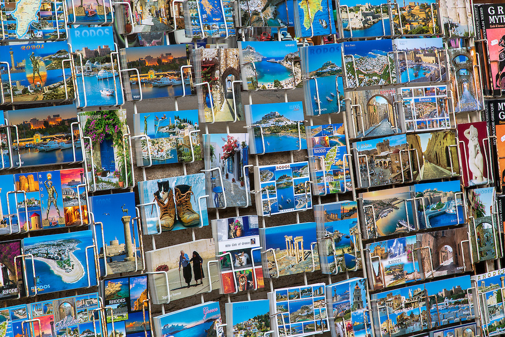 a large selection of postcards available to tourists on the island of Rhodes. The postcards show popular scenes throughout the large popular tourist island.
