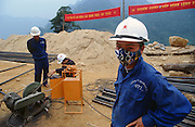 """February 2005 - Quang Binh, Vietnam - Military workers and members of the Vanguard Youth or """"compulsory workers"""" are commissioned by the government to repair this section of the remote Trung Son Highway or the 'New' Ho Chi Minh road as it traverses through the jungle at the Da Deo pass. This section was the scene of an enormous landslide and after four months of working they are yet to finish and secure the area. The location of much fighting during the Viet Nam war, this remote jungle is still the site of many landmines and MIA's. The road, started in April 2000, travels north of Ho Chi Minh (formerly Saigon) for over 2000km following the old routes of the Ho Chi Minh trails and it is believed by the Government that this road will open up this remote region of Vietnam. It is a belief that is disregarded by most foreign governments as the Viet Nam government has already invested over US$700m in the project, twice its budgeted amount. This area is the problem; an area of frequent landslides and malaria, making the continuous repair work long and hazardous for the workers. Photo Credit: Luke Duggleby"""
