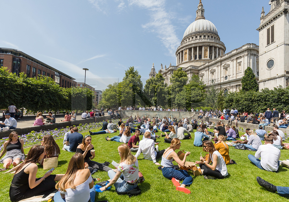 © Licensed to London News Pictures. 28/06/2019. London, UK.  Office workers and tourists enjoy the warm and sunny weather near St Paul's Cathedral in London on Friday lunchtime. A heatwave is forecast across much of the UK tomorrow, with temperatures in the capital expected to reach 33 degrees celcius.  Photo credit: Vickie Flores/LNP