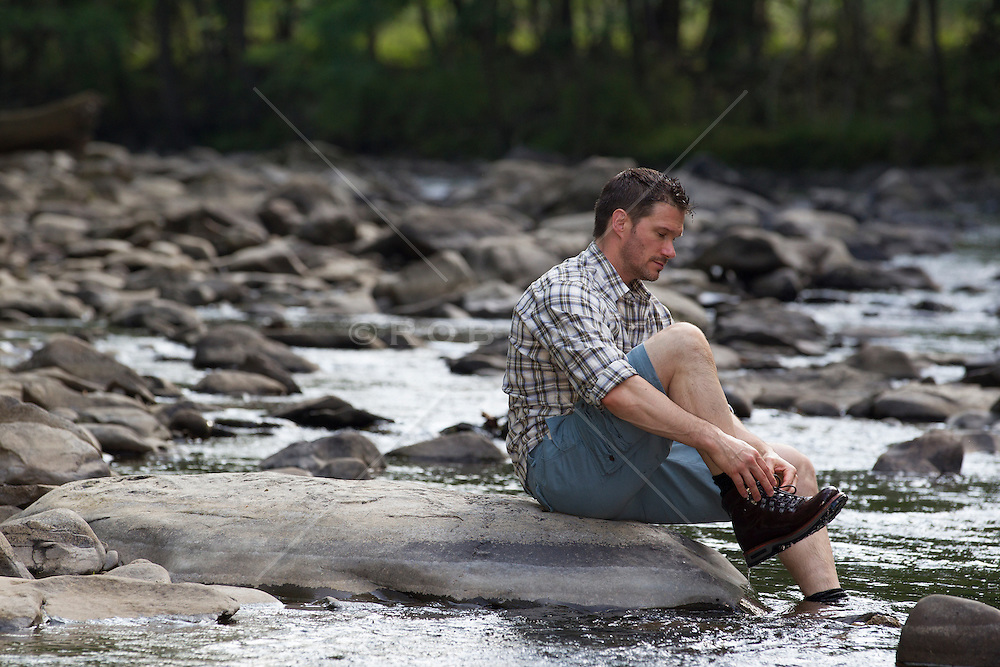 rugged man outdoors at a stream in Upstate New York fixing his hiking boot
