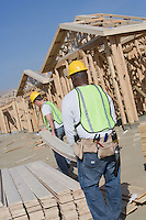 Two construction workers carrying wooden plank on site