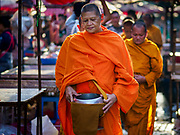 """04 DECEMBER 2018 - BANGKOK, THAILAND:  Buddhist monks walk through a market street cluttered with discarded single use plastic bags in Khlong Toei market. The issue of plastic waste became a public one in early June when a whale in Thai waters died after ingesting 18 pounds of plastic. In a recent report, Ocean Conservancy claimed that Thailand, China, Indonesia, the Philippines, and Vietnam were responsible for as much as 60 percent of the plastic waste in the world's oceans. Khlong Toey (also called Khlong Toei) Market is one of the largest """"wet markets"""" in Thailand. December 4 was supposed to be a plastic free day in Bangkok but many market venders continued to use plastic.     PHOTO BY JACK KURTZ"""