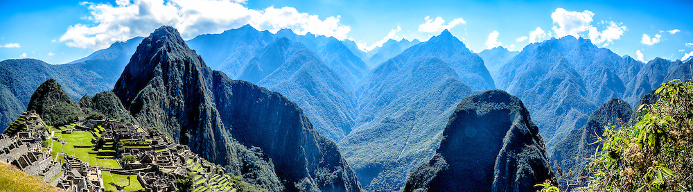 Machu PIcchu Ruins overlooking the Sacred Valley. On the left side of the image is Huayna Picchu mountain while center right is Putucusi Mountain