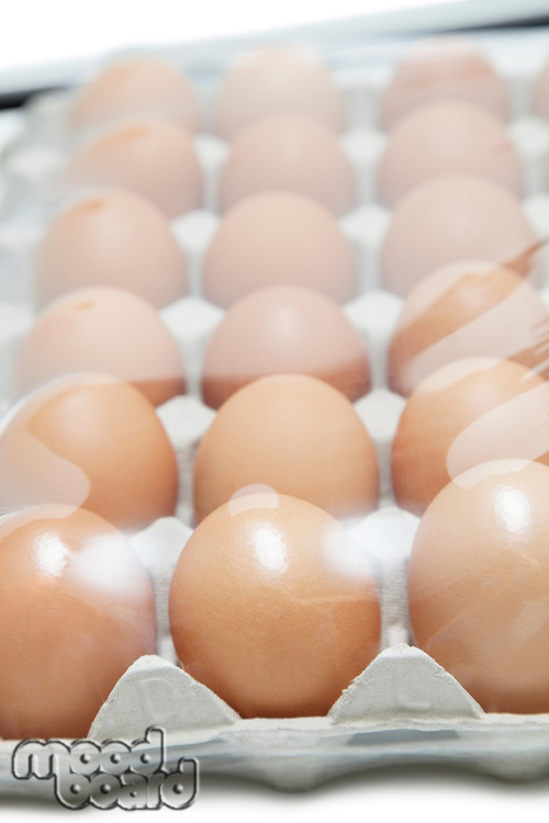 Brown eggs arranged in carton with plastic covering it