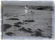 father with toddler and young child on the beach 1900s glass plate