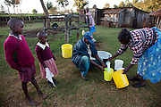 Kibet Serem and his sister-in-law Emily strain the milk from the family's five cows in their village near Kericho, Kenya. (From the book What I Eat: Around the World in 80 Diets. He is 25 years of age.) He cares for a small tea plantation that his father planted on their property near Kericho, Kenya when Kibet was a young boy and he is responsible for milking the cows that his family owns. He sells extra milk to a nearby school for a government feeding program and gives some to his mother who makes yogurt and sells it. His staple food is ugali, a maize meal porridge. He milks, feeds, waters and cares for the cows twice a day with the help of the wives of his brothers who also live on the property in their own houses.