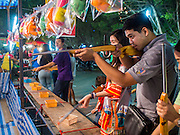 """07 MARCH 2015 - NAKHON CHAI SI, NAKHON PATHOM, THAILAND: A target shooting arcade game at the Wat Bang Phra tattoo festival. Wat Bang Phra is the best known """"Sak Yant"""" tattoo temple in Thailand. It's located in Nakhon Pathom province, about 40 miles from Bangkok. The tattoos are given with hollow stainless steel needles and are thought to possess magical powers of protection. The tattoos, which are given by Buddhist monks, are popular with soldiers, policeman and gangsters, people who generally live in harm's way. The tattoo must be activated to remain powerful and the annual Wai Khru Ceremony (tattoo festival) at the temple draws thousands of devotees who come to the temple to activate or renew the tattoos. People go into trance like states and then assume the personality of their tattoo, so people with tiger tattoos assume the personality of a tiger, people with monkey tattoos take on the personality of a monkey and so on. In recent years the tattoo festival has become popular with tourists who make the trip to Nakorn Pathom province to see a side of """"exotic"""" Thailand.   PHOTO BY JACK KURTZ"""