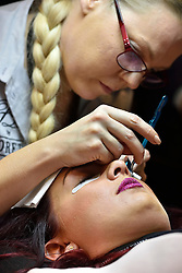 © Licensed to London News Pictures. 28/03/2016. A female visitor receives beauty treatment on her eye lashes at The Professional Beauty Show. The show is the largest in the UK and one of the largest in Europe. London, UK. Photo credit: Ray Tang/LNP