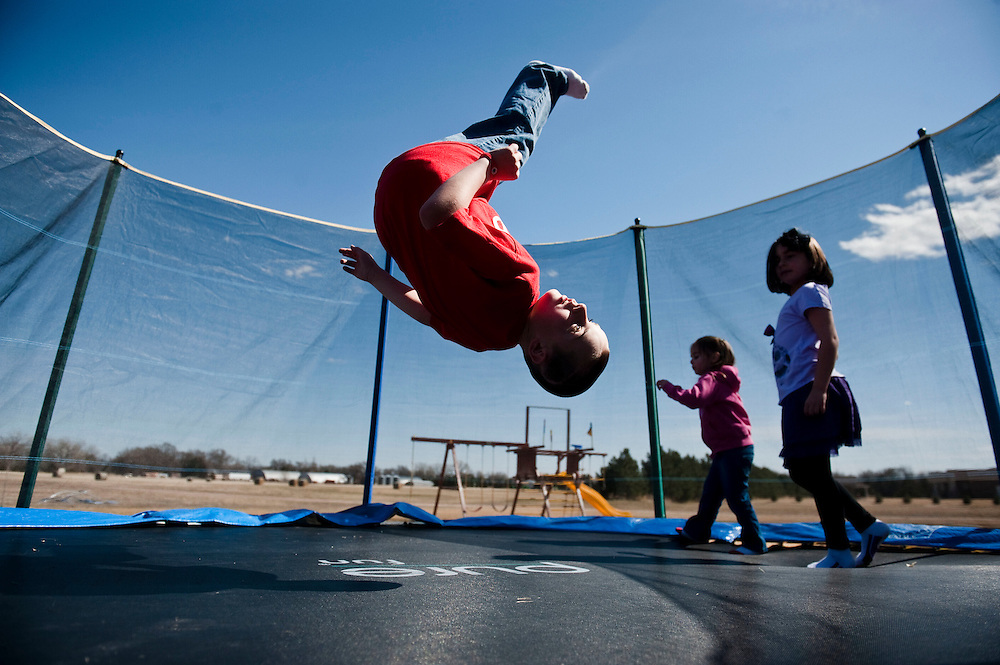 Atkinson, Neb.-04/10/2014- Jack Hoffman, 8, does a flip on the trampoline in his backyard April 10, 2014 while his two sisters, Reese, 3, left, and Ava, 6, walk around the edge. Jack was diagnosed with pediatric brain cancer at age 6 and underwent two life threatening brain surgeries. The Hoffman family wanted to give their son a chance to meet Rex Burkhead, a Nebraska football player, and since that meeting Jack has scored a touchdown in Nebraska's spring game, won an ESPY, and met President Obama in the Oval Office, among other memorable moments. Jack has been in remission since October 2013.<br />