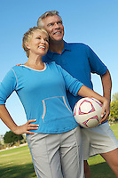 Senior couple holding soccer ball in park